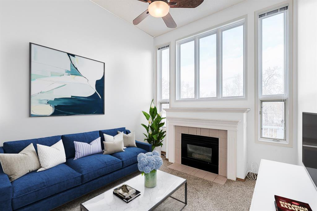 Living room space with huge windows, glass fireplace and 12' ceilings creates spectacular potential.   This is virtually staged + shows suggested minor reno (paint only), but is just one idea as to how it ciould be improved with some relativley minor work