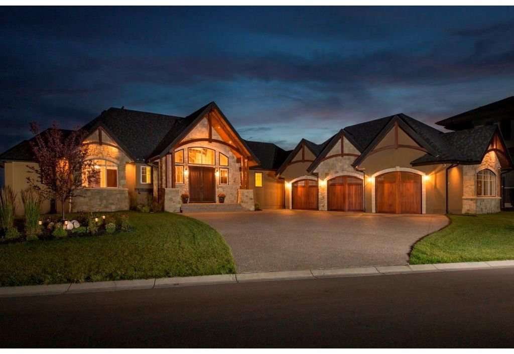 Exterior front with grand entrance, and extensive natural stone and cedar accents.
