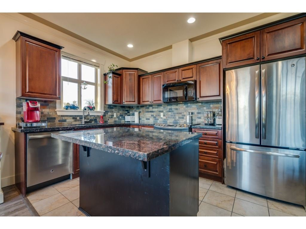 STUNNING open-plan kitchen with granite countertops, upgraded SS appliances and ample storage