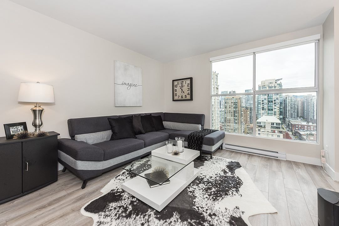 Spacious living room with views out over Heritage buildings of Yaletown and the North Shore mountains.
