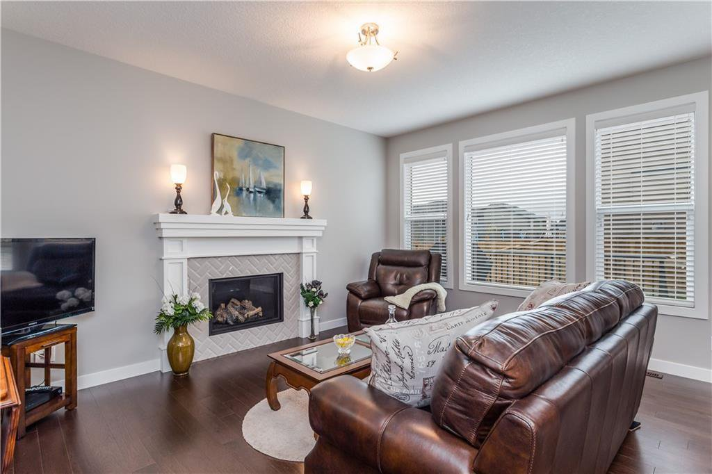 The elegant living room boasts a contemporary fireplace and large West facing windows - but central A/C will keep the temperature under control.