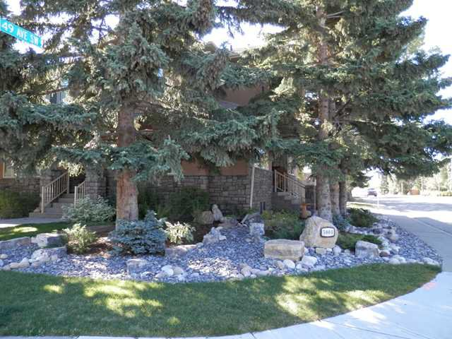 A beautifully landscaped corner lot with mature trees and well-maintained garden features.