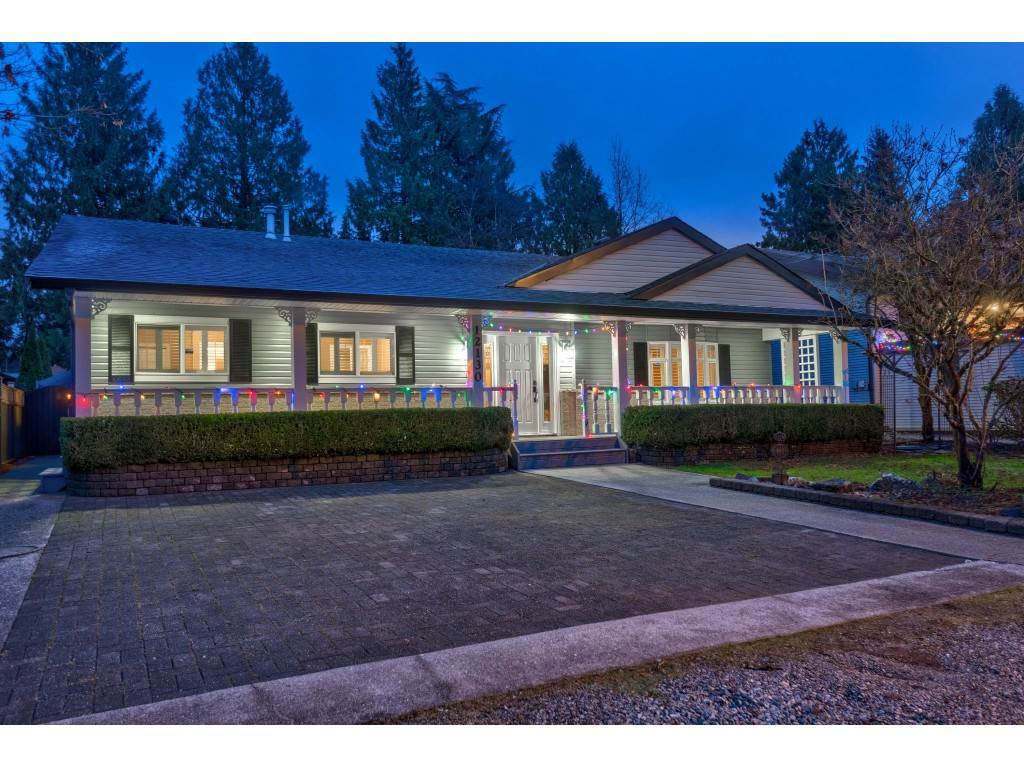 Stunning exterior features abundant car/RV parking and a 50-foot covered porch with latticework