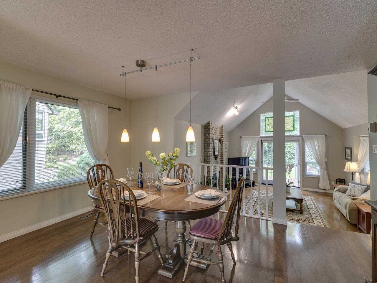Dining room overlooking vaulted, sunken living room with access to wrap around deck.