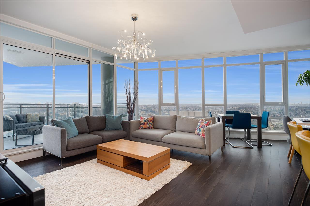 Large living room surrounded by south and southwest facing floor to ceiling windows for year round sunlight, warmth, and unobstructed views.