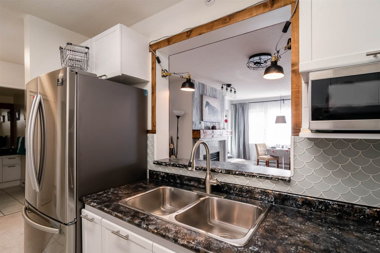 Beautifully renovated kitchen with white cabinets, stainless steel appliances and rusitic wood trim.
