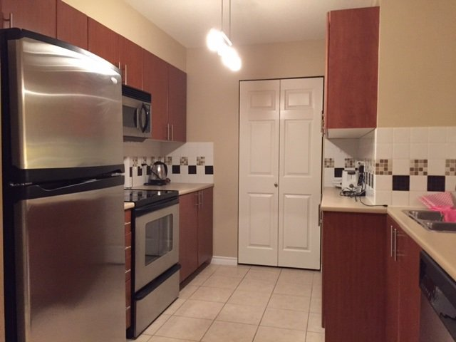Spacious Kitchen with stainless steel fridge and stove, lots of storage space including pantry.
