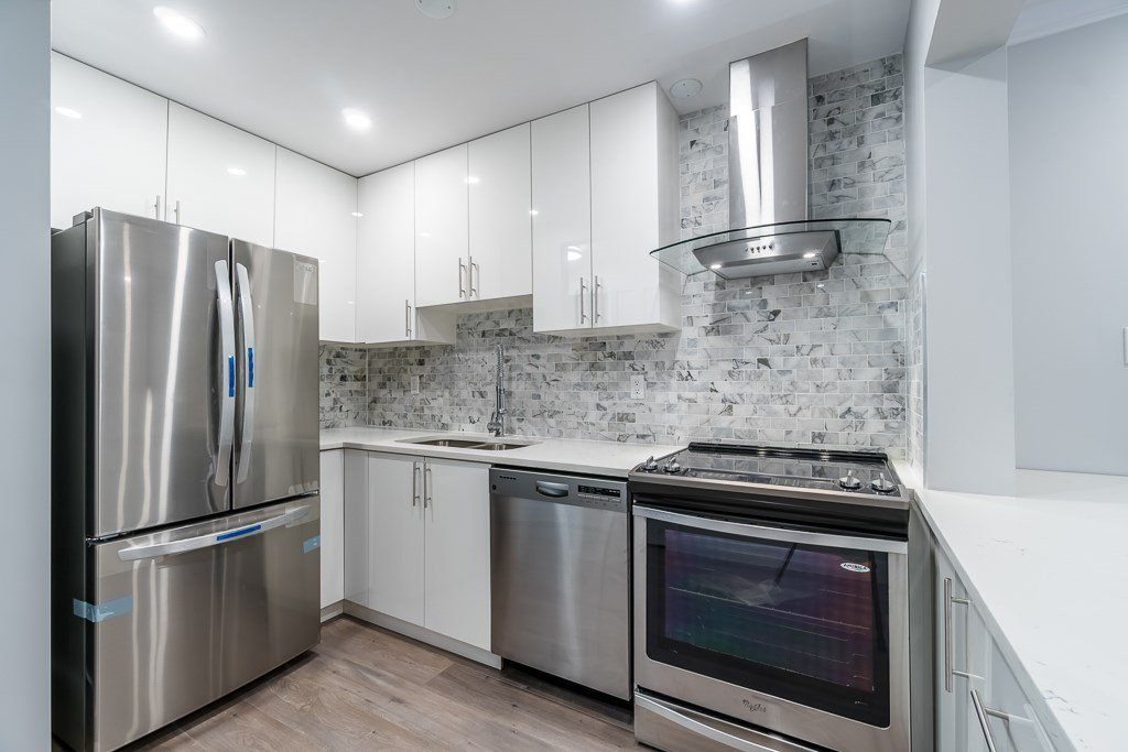 Complete renovated kitchen with backsplash tiles and stainless steel appliance.