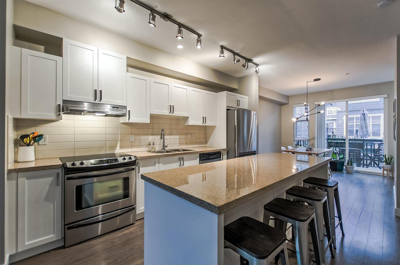 Double thick granite, white cabinets and stainless steel appliances.