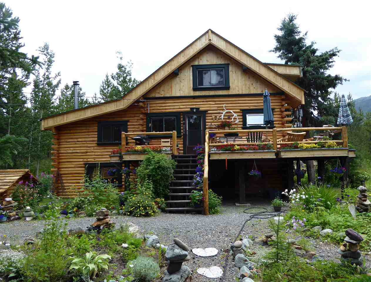 Beautiful log home tucked way back in the trees, backing onto Pine Creek and with a great landscaped yard with underground irrigation