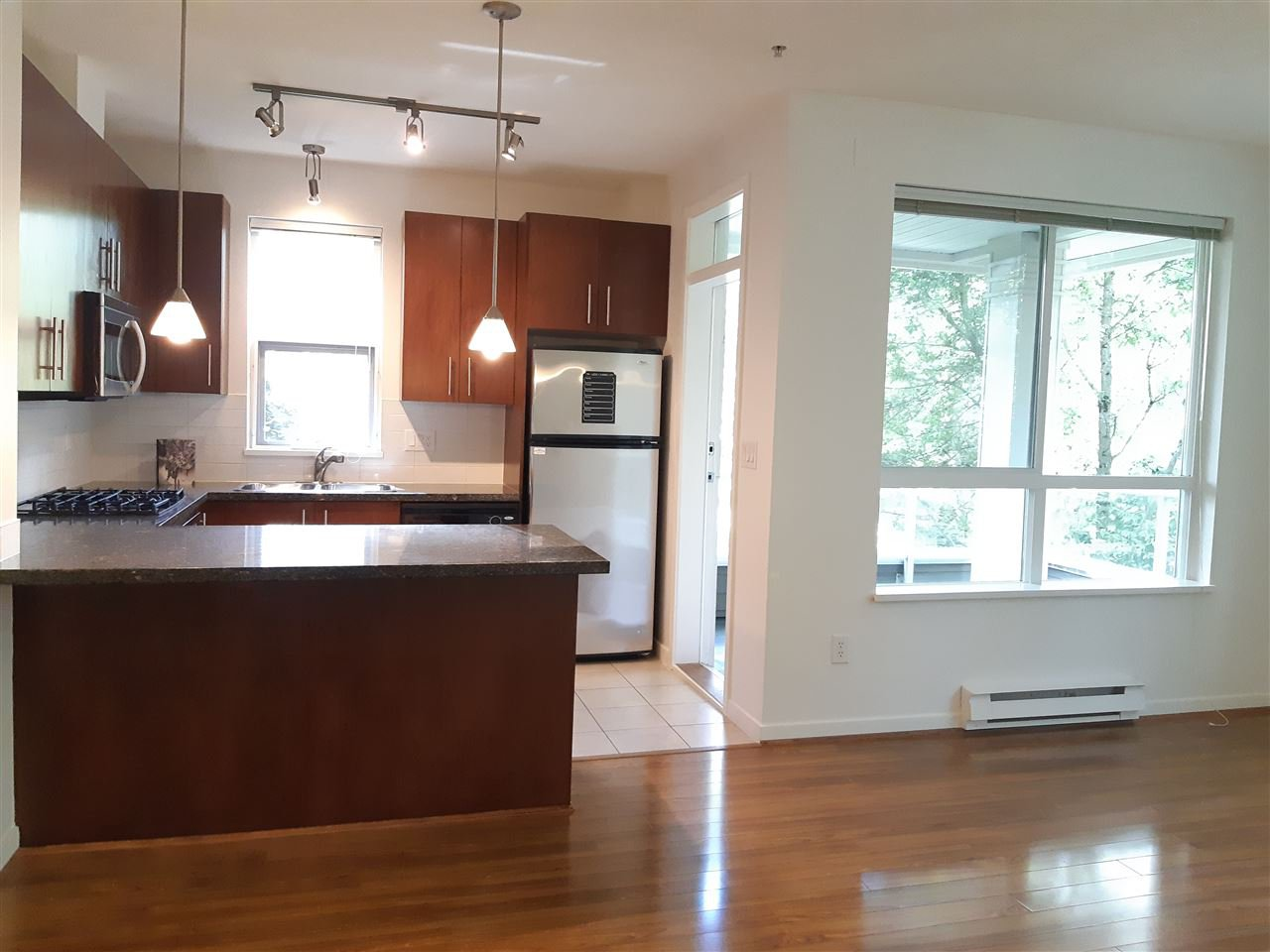 Window in kitchen and spacious balcony access.