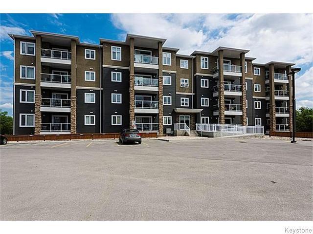 Front view, 6 visitor parking stalls, handicap accessible, underground garage door left side of building.