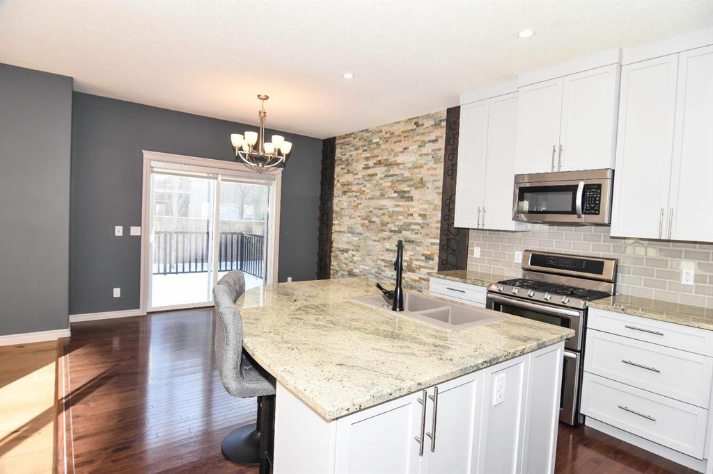 Chic open concept design with light cabinetry, stone accent dining room wall, quartz counters!