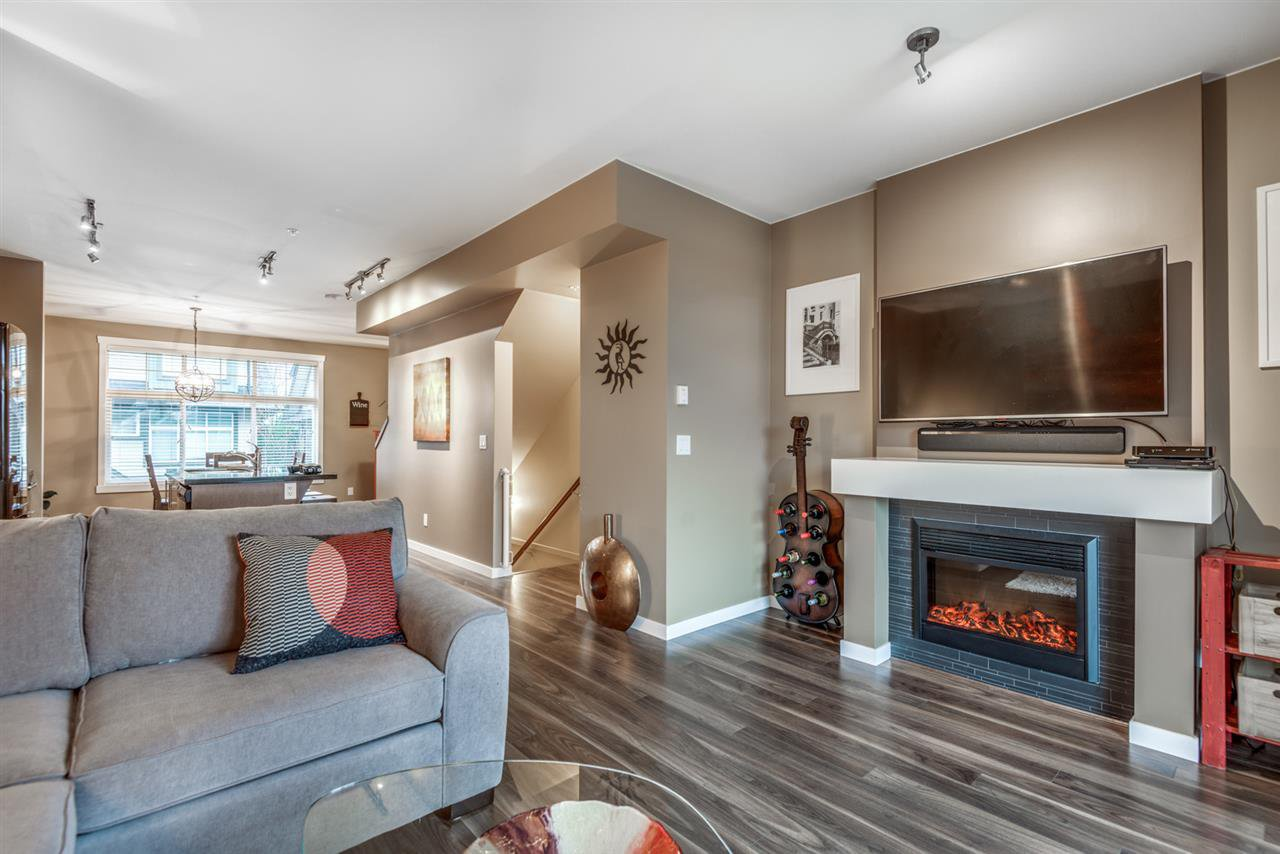 Cozy living room with electric fireplace and sliding doors to a fenced private backyard.