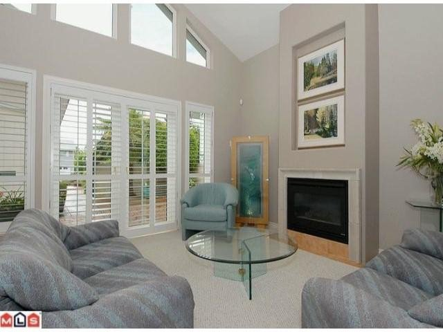 Light & bright high ceilings & cozy fireplace with french doors to patio enhance this lovely livingroom.