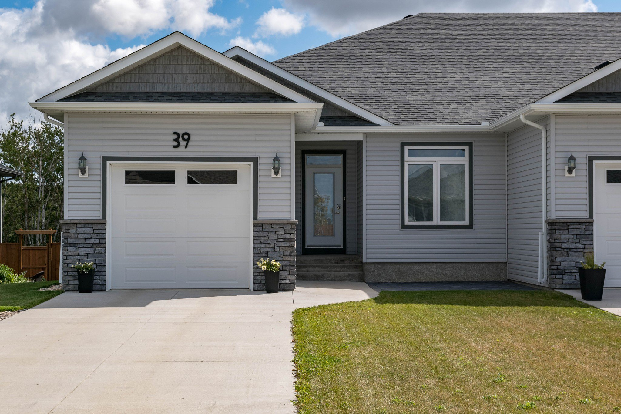 GREAT VALUE! 1407 sf 2+ bedroom side attached raised bungalow backing onto green space in Town of Oakbank. Oversized 24.6x13.6 insulated & drywalled AT1, concrete driveway.