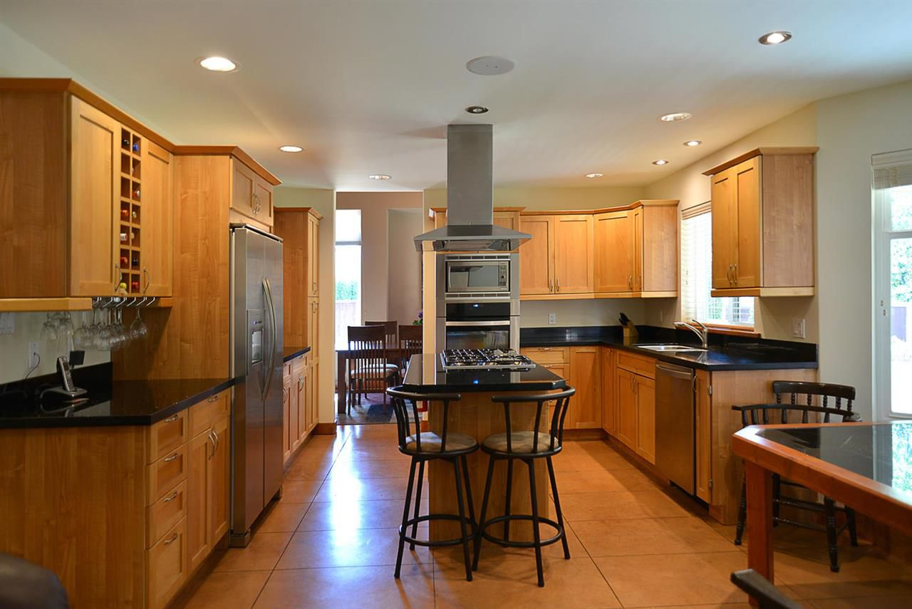 Gourmet kitchen with central n/g cooktop, Meile stainless steel appliances, fridge with ice maker, granite counter tops, with built in eating area. View to family room with a natural gas fireplace and garden doors lead to bright and spacious patio.