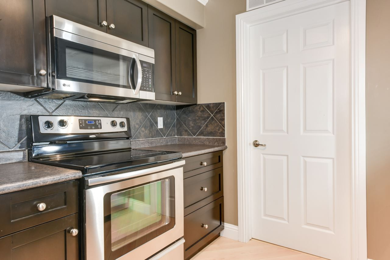 Espresso maple cabinets, tile backsplash, stainless steel appliances
