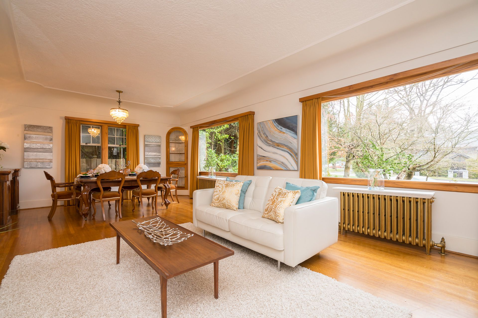 Large main living room with dining area and woodburning fireplace. Tons of natural light from large windows