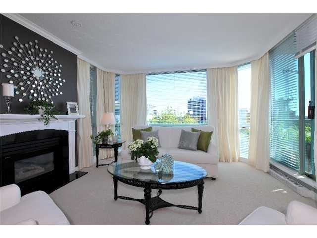Spacious living rooom features beautiful natural gas fireplace, deck access, floor to ceiling windows, and views of the city and water.