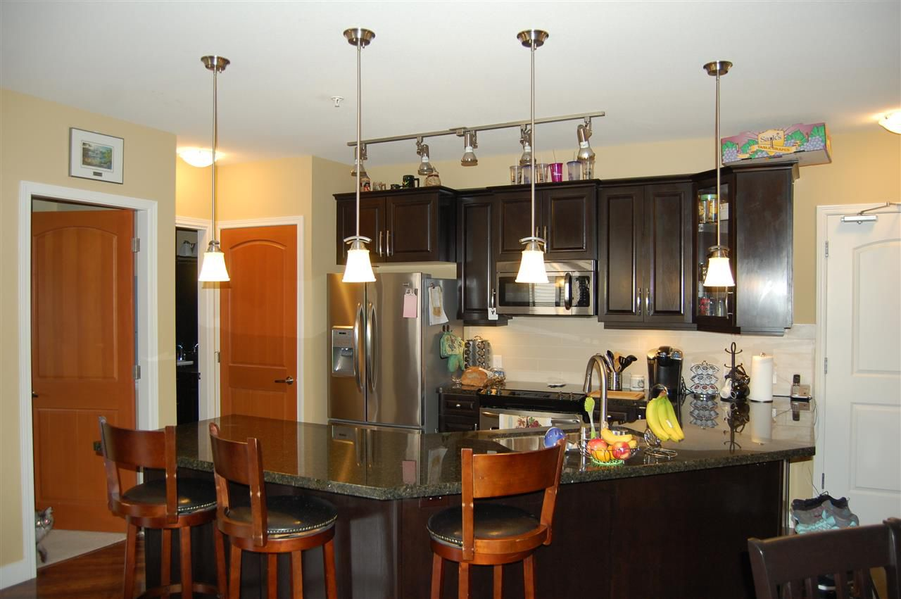 Granite counter top with eating bar; dishwasher and SS fridge with water/ice