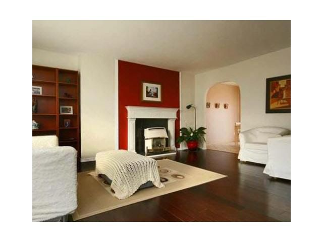 Spacious and bright living room features beautiful updated laminate floor and a fireplace.
