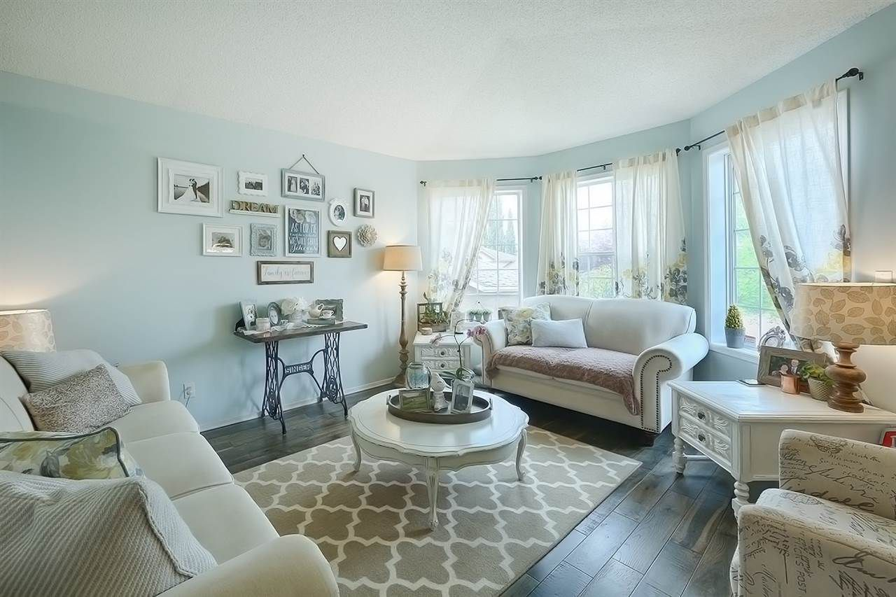 Right out of a magazine! The living room is beautiful and bright, thanks to the large windows and vaulted ceilings. Stunning hardwood floors lend to the beauty of this space.