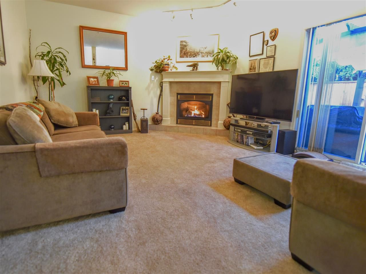 Large sunken living room with cozy natural gas fireplace and walk out to patio & fenced yard.
