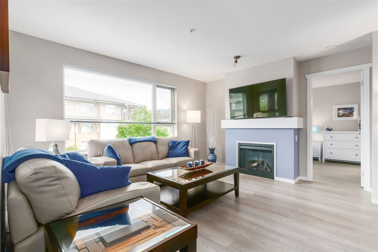 The living room is bright and spacious, and features an electric fireplace.