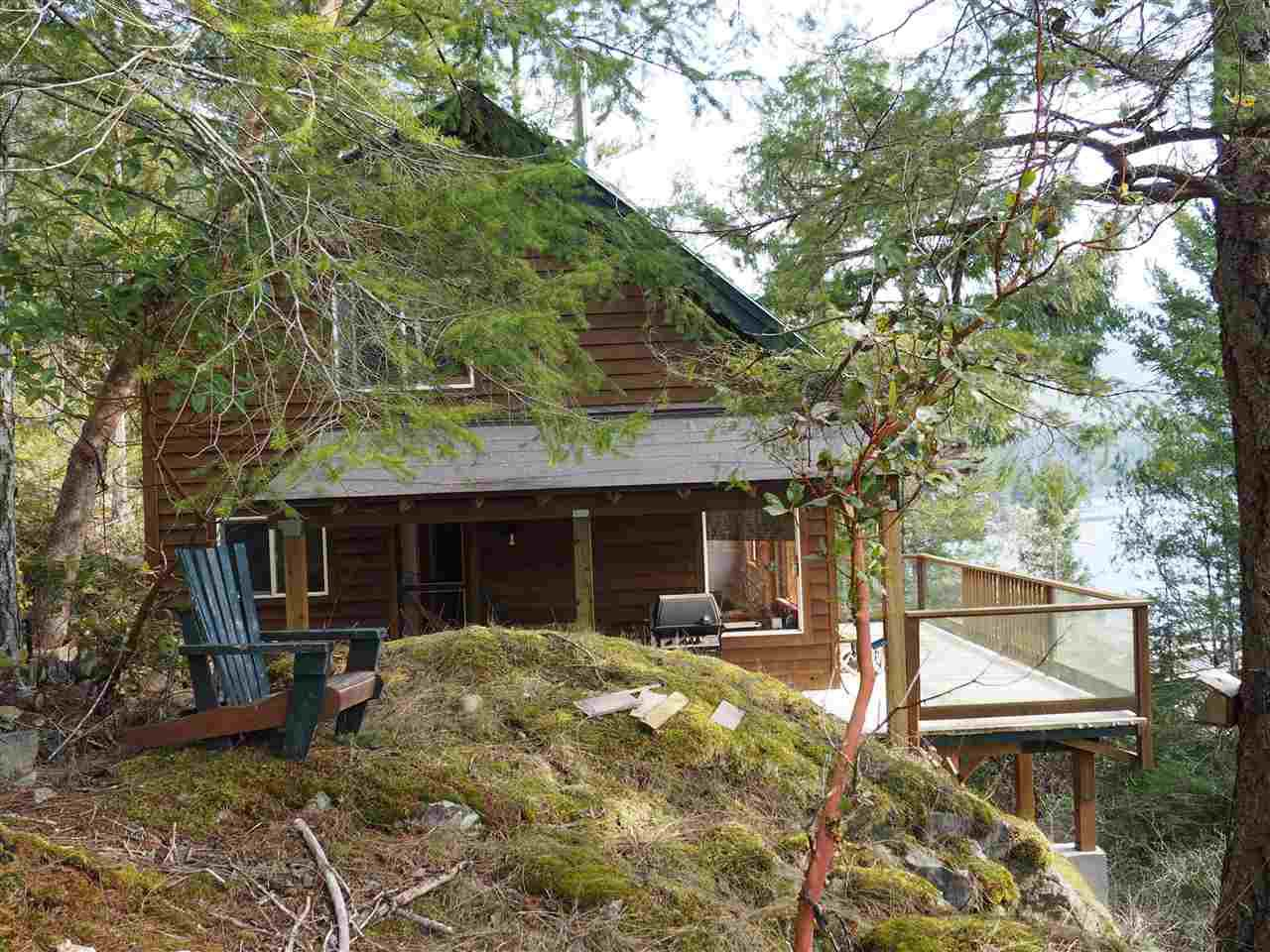 Cabin perched on the moss-covered bluff.